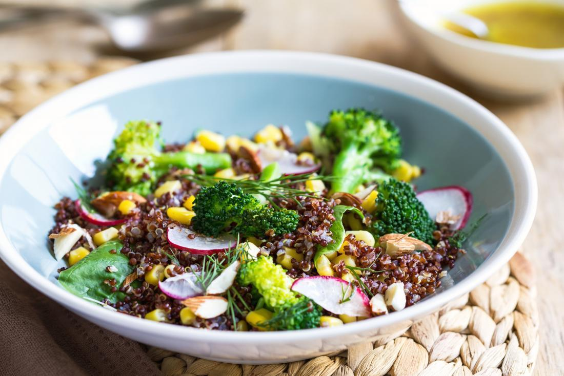 Broccoli salad in bowl with quinoa and radish and sweetcorn.