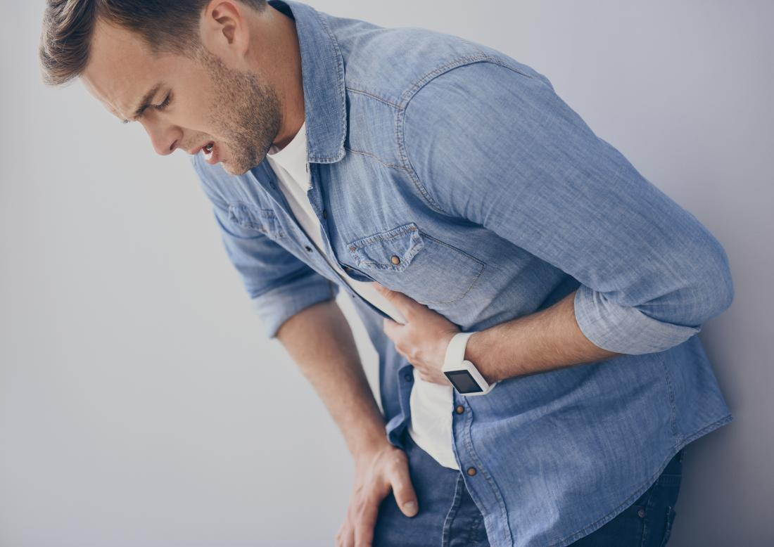 Man with gastritis leaning over and holding his stomach in pain.